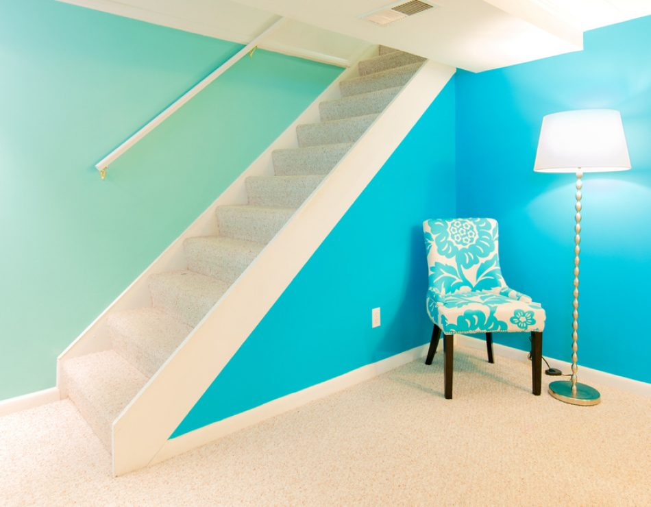 Bright carpet and fresh, contemporary colors make this finished basement light and airy. It is a finished basement common in a typical American home.